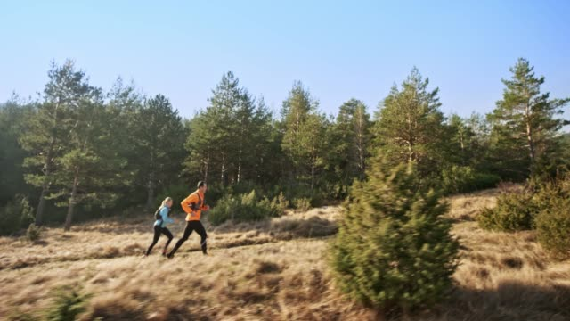 TS Couple running up a sunny mountain trail in early spring