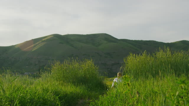 Couple running up hill in green rolling landscape / Salt Lake City, Utah, United States