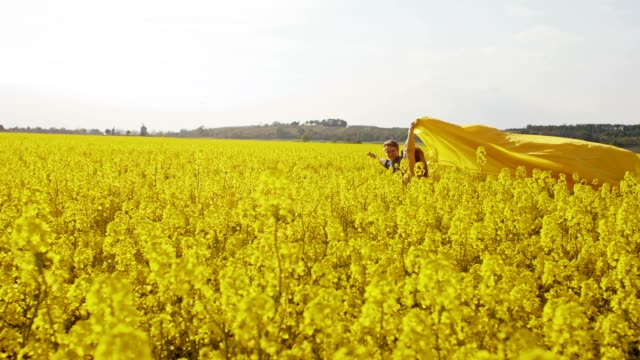 slo mo couple running with a shawl among blooming canola - shawl stock videos & royalty-free footage