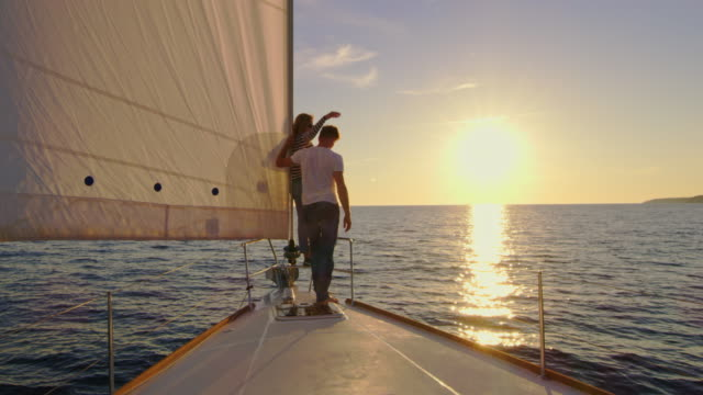 vídeos de stock e filmes b-roll de slo mo couple sailing at sunset - vela desporto aquático