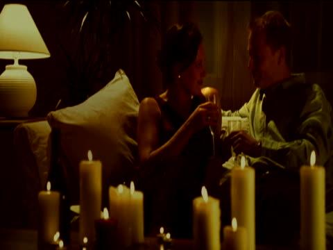 vídeos y material grabado en eventos de stock de couple sat together on a sofa surrounded by candles, drinking wine and kissing - encuadre de tres cuartos