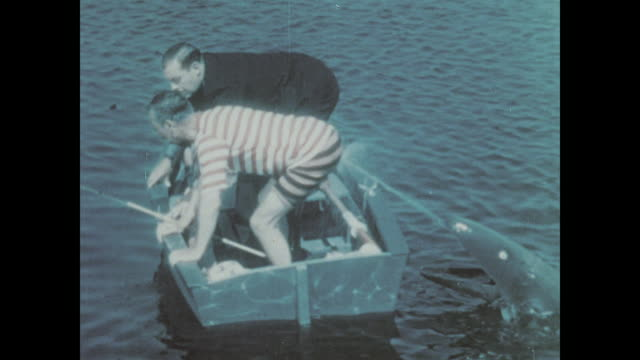1930 a couple scare two men on a rowboat - spraying stock videos and b-roll footage