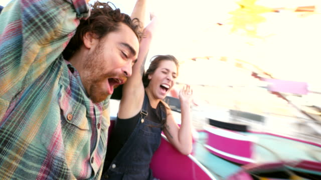 cu couple screaming and laughing while riding amusement park ride - avventura video stock e b–roll