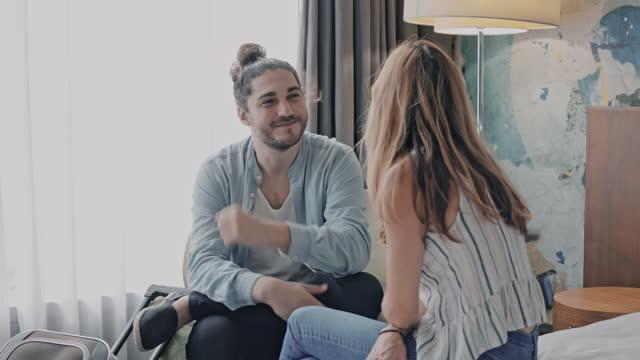 vidéos et rushes de couple assis confortablement dans leur chambre d'hôtel et planifiant leur excursion d'une journée - boyfriend