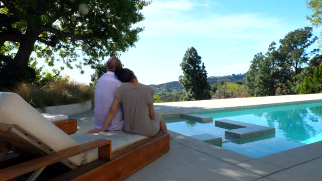 ws pan couple seated together on lounge chair by pool - completely bald stock videos & royalty-free footage