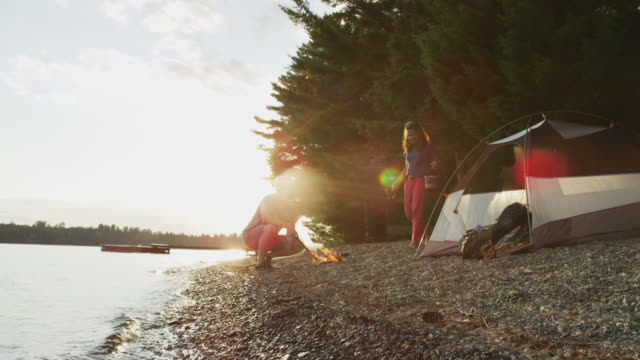couple setting camp on the shore of sebec lake - lagerfeuer stock-videos und b-roll-filmmaterial