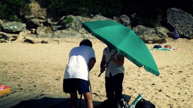 vídeos y material grabado en eventos de stock de ajuste par encima de parasol de playa - instalar