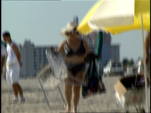 couple setting up chairs and umbrella on the beach in miami, florida - anno 1994 video stock e b–roll