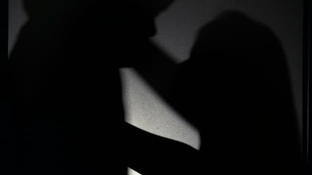 vídeos de stock e filmes b-roll de couple shadow tenderly kissing in silhouette - retroiluminado