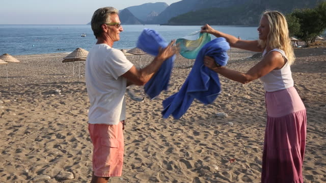 vídeos de stock e filmes b-roll de couple shake towels out after beach break - toalha
