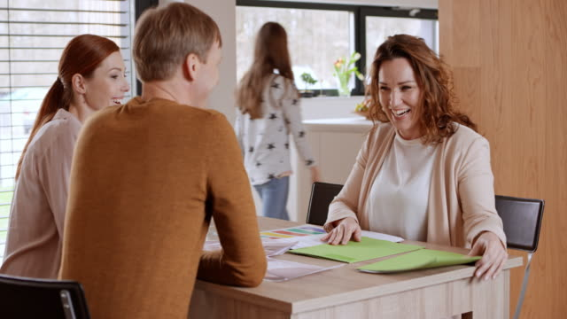couple shaking hands with a female interior designer at a meeting in their house - table top shot video stock e b–roll