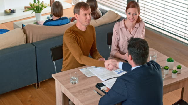 Couple shaking hands with a male banker at a meeting in their home