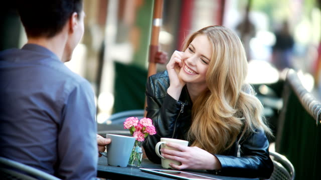 Couple share a latte at sidewalk cafe