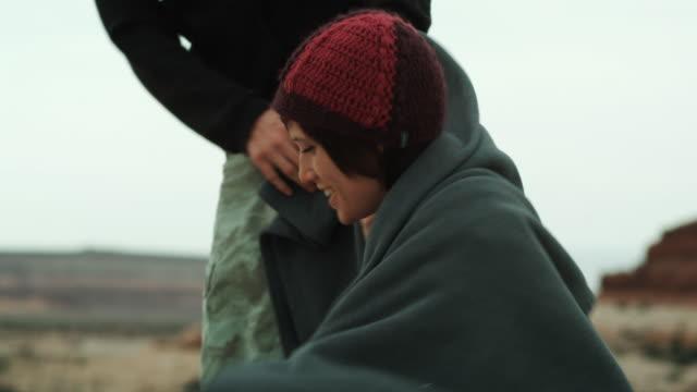 vídeos y material grabado en eventos de stock de couple sharing a blanket in the desert - camisa con capucha