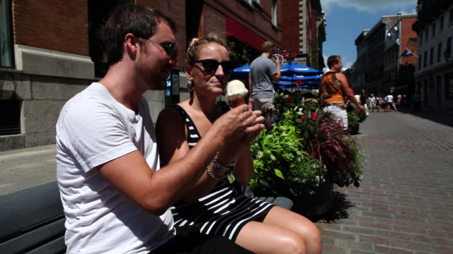 MS Couple sharing maple syrup flavored ice cream cone in old montreal in hot summer day / Montreal, Quebec, Canada