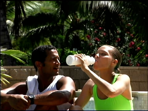 stockvideo's en b-roll-footage met couple sharing water bottle outdoors - mid volwassen koppel