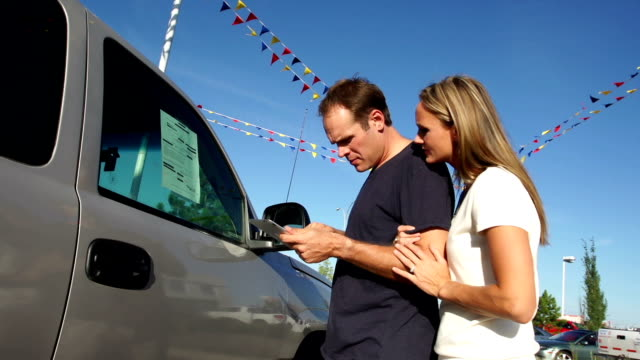 couple shop for a vehicle - mid adult men stock videos & royalty-free footage