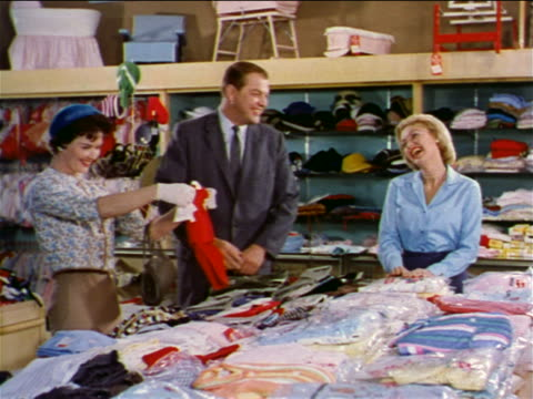 vidéos et rushes de 1962 couple shopping for baby clothing + saleswoman laughing in department store / industrial - homme dans un groupe de femmes