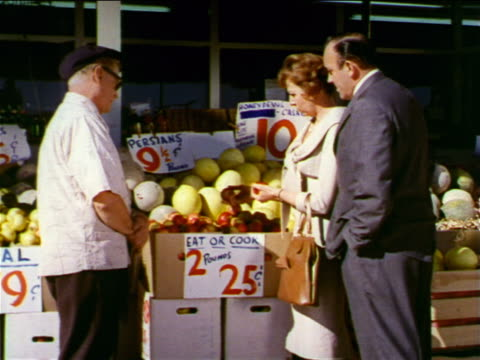 1962 couple shopping for fruit at outdoor fruit stand with senior salesman / industrial - greengrocer stock videos & royalty-free footage