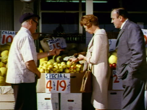 1962 couple shopping for fruit at outdoor fruit stand with senior salesman / industrial - salesman stock videos & royalty-free footage