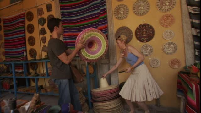 vídeos y material grabado en eventos de stock de ms pan couple shopping for souvenirs and trying on sombreros in tourist gift shop / merida, mexico  - falda