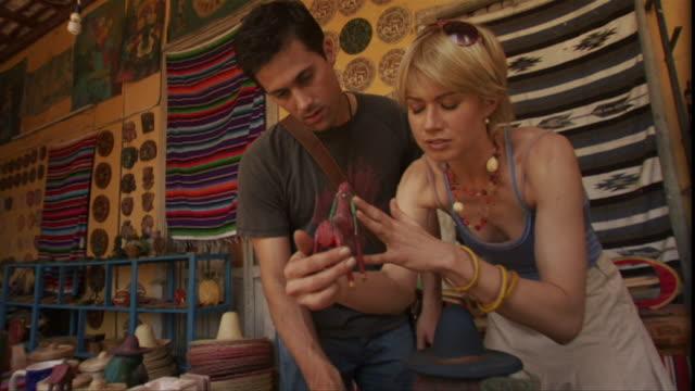LA MS Couple shopping for souvenirs in tourist gift shop / Merida, Mexico