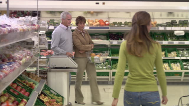 vídeos de stock, filmes e b-roll de ms couple shopping fruit and vegetable in supermarket / north finchley, london, uk - mulheres de idade mediana