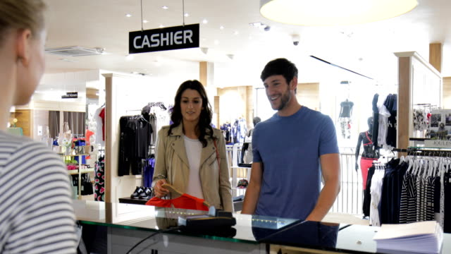 couple shopping in a clothing store - clothing store stock videos and b-roll footage