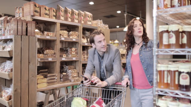 stockvideo's en b-roll-footage met couple shopping in a deli together - glazen pot