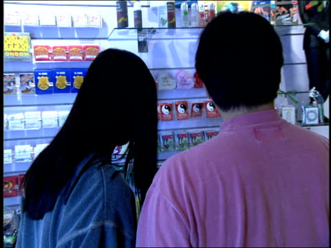 couple shopping in condom store - condom stock videos and b-roll footage