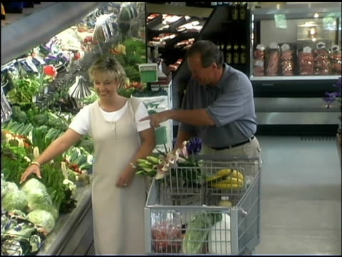 vidéos et rushes de couple shopping in grocery store - caddie