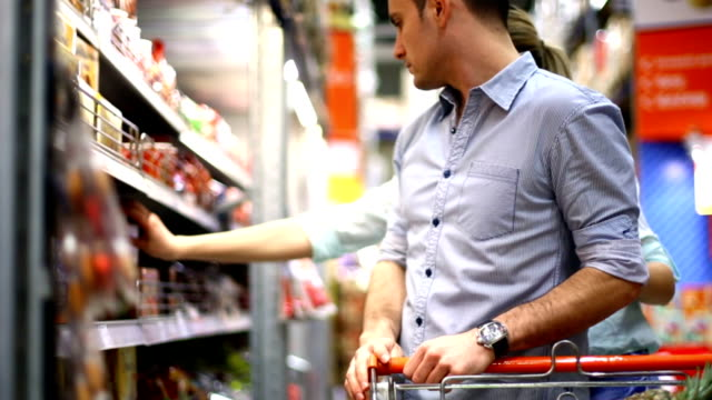 stockvideo's en b-roll-footage met couple shopping in supermarket. - supermarkt