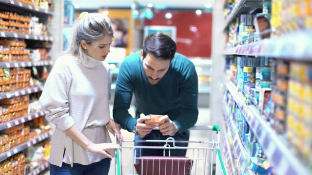 couple shopping in supermarket. - shelf stock videos and b-roll footage