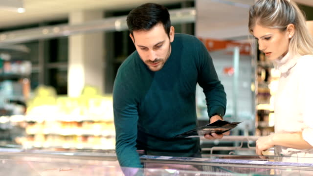 couple shopping in supermarket. - shopping basket stock videos and b-roll footage