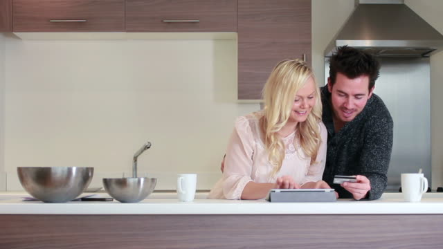 couple shopping online in kitchen