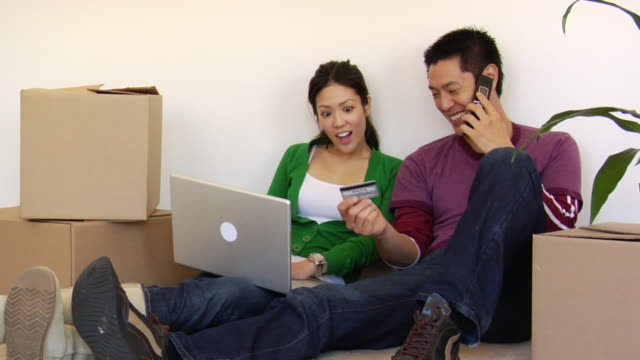ms couple shopping online with credit card while using laptop and talking on cell phone among moving boxes / los angeles, california, usa - financial accessory stock videos & royalty-free footage