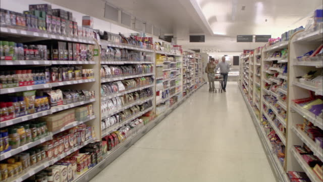 WS PAN POV Couple shopping with pulling trolley in supermarket / North Finchley, London, UK