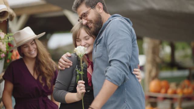 couple shops for flowers at a mobile flower shop, boyfriend gives woman a single flower - smelling stock videos & royalty-free footage