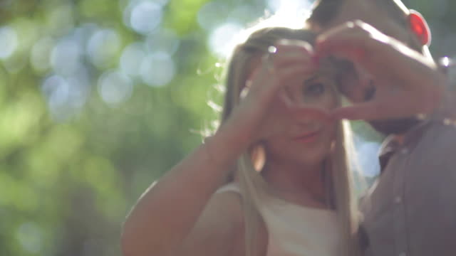 close up selective focus couple showing heart hand sign in forest on sunny day - less than 10 seconds stock videos & royalty-free footage