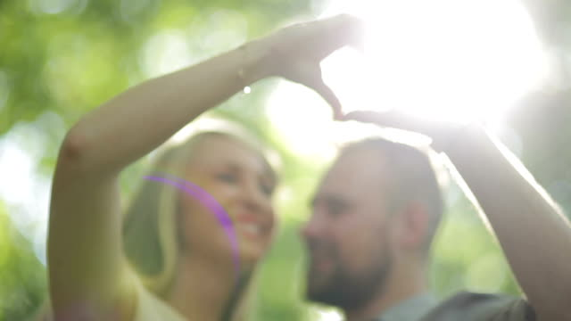 CLOSE UP LOW ANGLE Couple showing heart hand sign in forest on sunny day