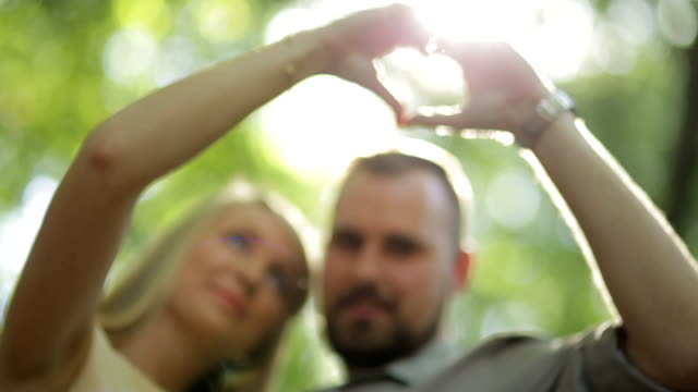 close up low angle couple showing heart hand sign in forest on sunny day - less than 10 seconds stock videos & royalty-free footage