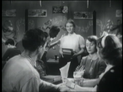 b/w 1951 couple showing off to group of teens at table in malt shop - 1951 stock videos & royalty-free footage