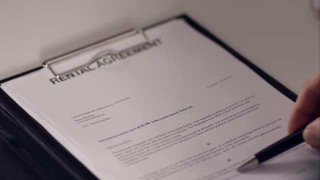 paar unterzeichnung vertrag für neue apartment - immobilienschild stock-videos und b-roll-filmmaterial