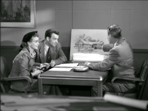 b/w 1953? couple signing contract with real estate agent in office - femmina con gruppo di maschi video stock e b–roll