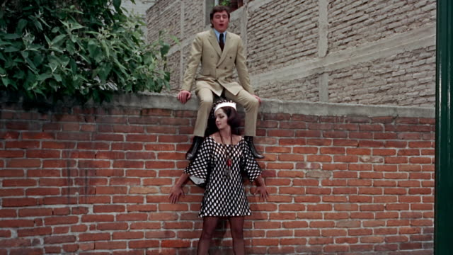 vídeos de stock, filmes e b-roll de couple singing and dancing on a wall in the street - 1960 1969
