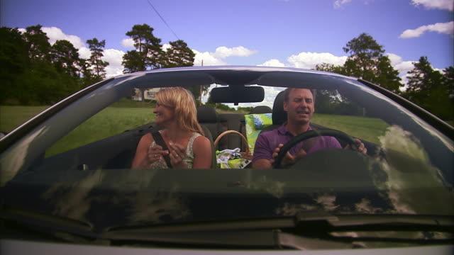 a couple singing in a cabriolet vallentuna sweden. - フロントガラス点の映像素材/bロール