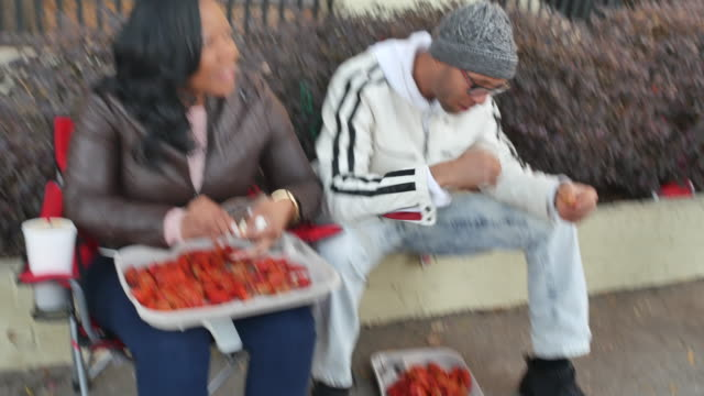 a couple sit and eat crawfish on st charles street after the krewe of thoth parade during mardi gras - アメリカ南部点の映像素材/bロール