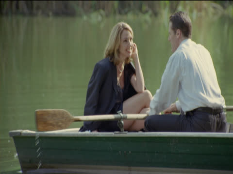 couple sit face to face in a river boat, flirting, man rows the boat, central park, new york - dreiviertelansicht stock-videos und b-roll-filmmaterial