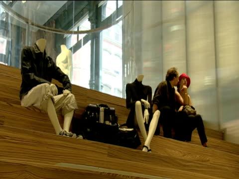 couple sit next to mannequins displayed on wooden steps in designer boutique new york - exklusiv stock-videos und b-roll-filmmaterial