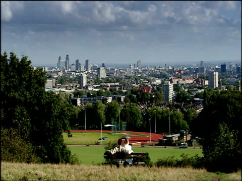 couple sit on bench on hampstead heath and look out over skyline london - natural parkland stock videos & royalty-free footage
